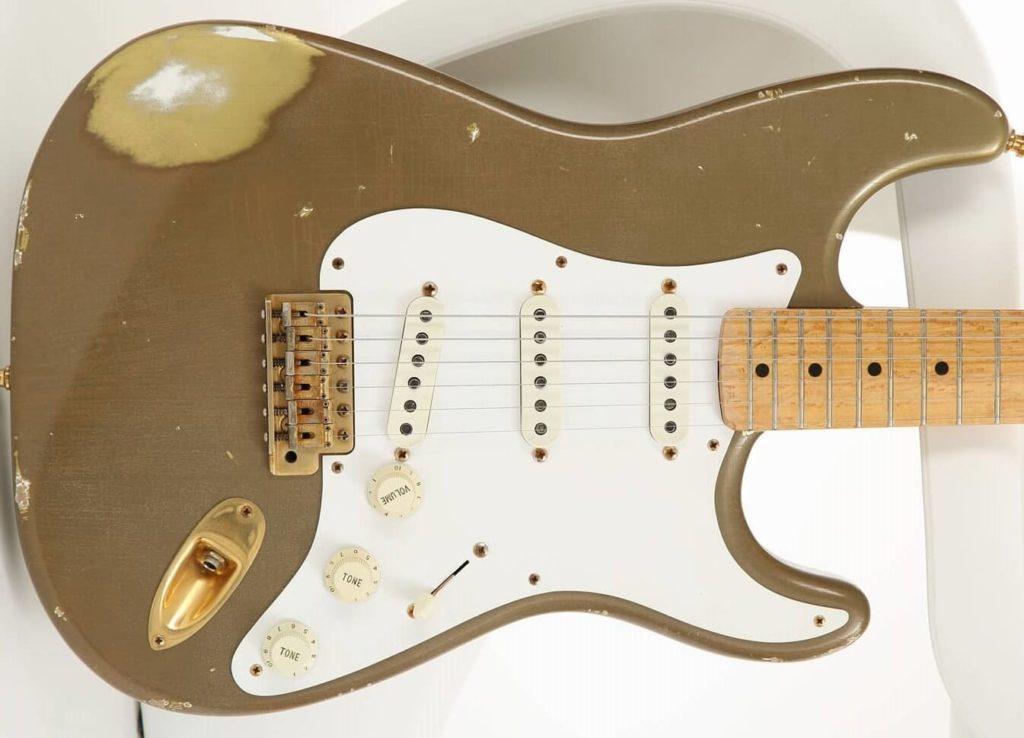 Foto de um corpo de Stratocaster com acabamento em relíquia de ouro e ferragens