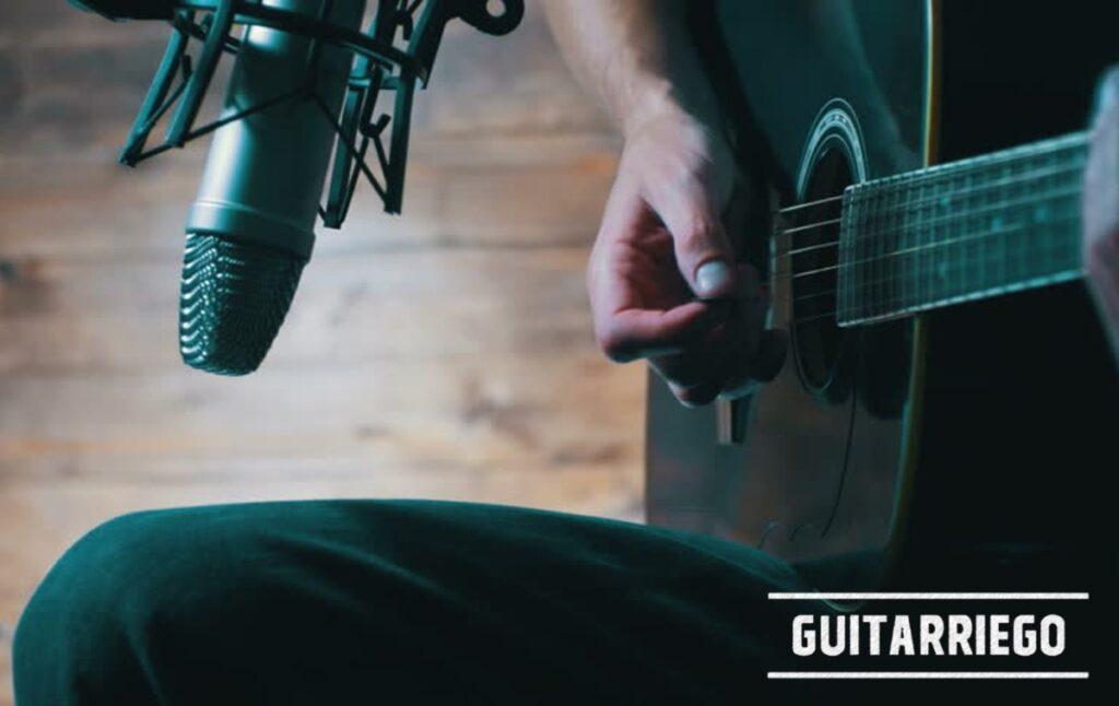 Grabando una canción con la guitarra frente al micrófono.